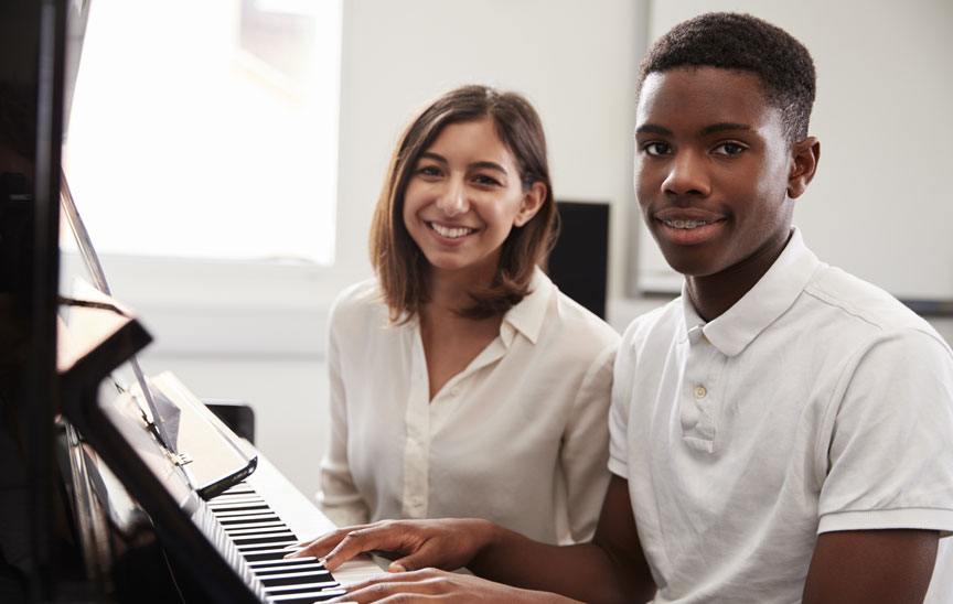 Boy with teacher at piano